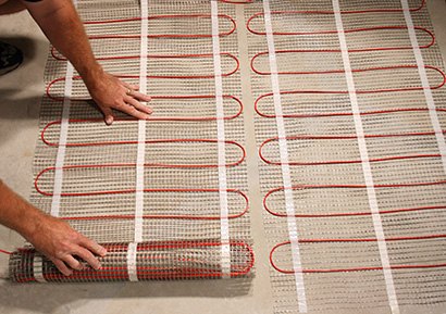 Laying out ComfortTile floor heating mats for heated bathroom floor.